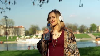 Happy girl listening music and drinking water in the park