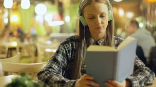 Happy girl listening music and reading book in the cafe