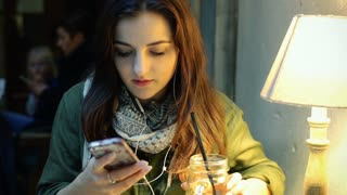 Happy girl listening music on earphones and texting on smartphone