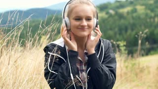 Happy girl listening music on headphones and enjoying it very much
