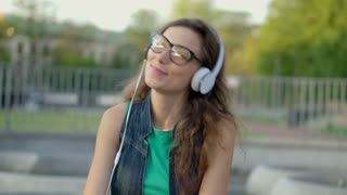Happy girl listening music on headphones and smiling to the camera