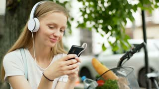 Happy girl listening music on headphones and texting on smartphone