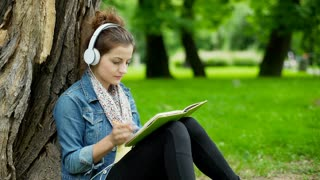 Happy girl listening music on headphones and writing in notebook in the park