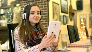 Happy girl listening music on headphones while relaxing in the cafe, steadycam s