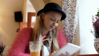 Happy girl looking stylish while wearing bowler hat and reading book in the cafe