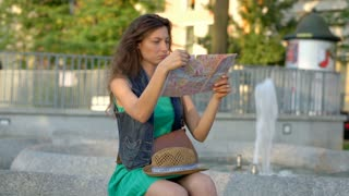 Happy girl reading map and smiling to the camera while sitting next to the fount