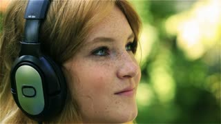 Happy girl relaxing and listening music on headphones, steadycam shot
