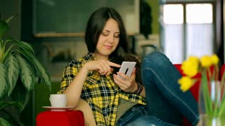 Happy girl sitting on the red couch and using smartphone
