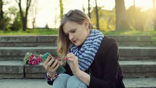 Happy girl sitting on the stairs and texting on smartphone