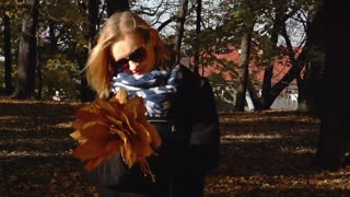 Happy girl standing in park with bunch of leaves, steadycam shot, slow motion sh