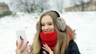 Happy girl standing in the snowy park and having a videochat on smartphone
