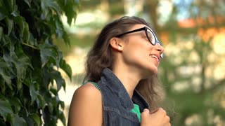 Happy girl standing outdoors and relaxing, steadycam shot, slow motion shot