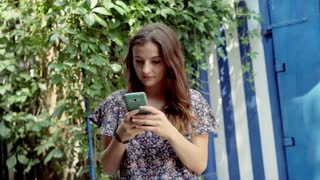 Happy girl standing outside and texting messages on smartphone