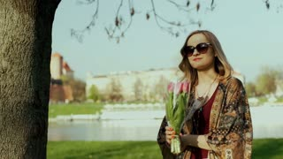 Happy girl taking off sunglasses and smelling bunch of tulips