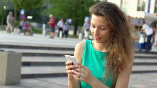 Happy girl texting messages on smartphone, steadycam shot, slow motion shot at 2