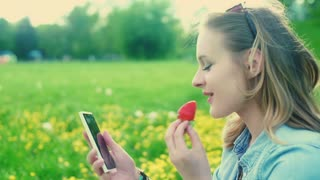Happy girl texting on smartphone and eating strawberry on the meadow