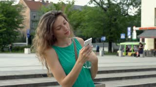 Happy girl texting on smartphone in the city, steadycam shot, slow motion shot a