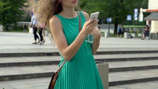 Happy girl texting on smartphone in the city, steadycam shot, slow motion shot