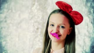 Happy girl wearing red bow and playing with moustache, steadycam shot