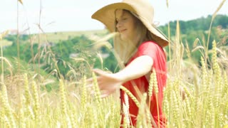 Happy girl wearing straw hat and turning around in the grain field
