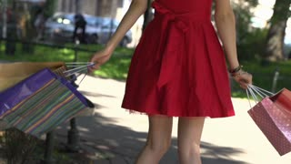 Happy girl with shopping bags going round, slow motion shot