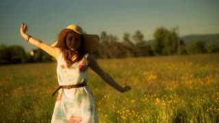 Happy girl with straw hat standing on the meadow and looking to the camera