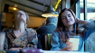 Happy girlfriends sitting together in the cafe and relaxing