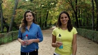 Happy jogger walking in the park with energy drink, steadycam shot