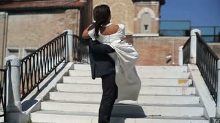 Happy just married groom carry on his hands the bridge in Venice