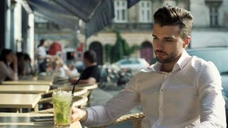 Happy man drinking refreshing mojito and smiling to the camera