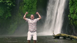 Happy man feeling free and jumping next to the waterfall, slow motion shot