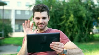 Happy man holding tablet and having a videocall while sitting in the park