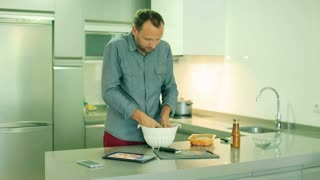 Happy man mixing salad with hands in the kitchen