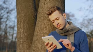 Happy man standing next to the tree and browsing internet on tablet, steadycam s