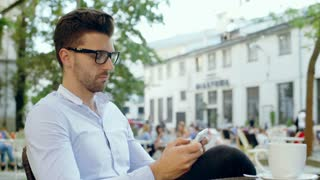 Happy man thinking while texting message on smartphone in the outdoor cafe