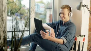 Happy man wearing headphones and having a videocall on tablet