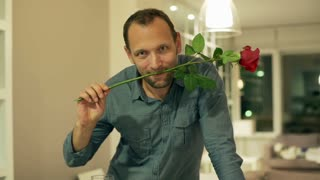 Happy man with rose and wine flirting to the camera