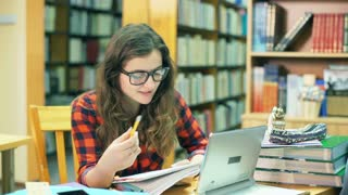 Happy student doing homework in the library and having a videocall on tablet