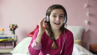 Happy teenager listening music on headphones and smiling to the camera