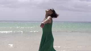 Happy woman dancing on the beach, slow motion shot at 240fps