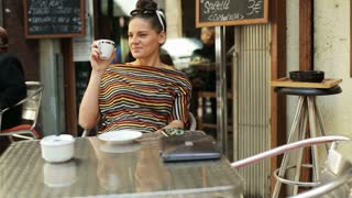 happy woman drinking coffee by the table and smiling to the camera