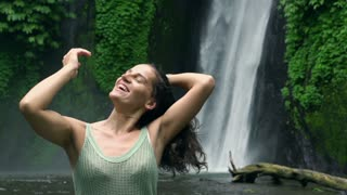 Happy woman feeling free next to the waterfall, slow motion shot at 240fps