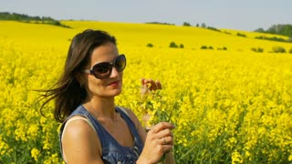 Happy woman holding bunch of rapeseeds, steadycam shot, slow motion shot