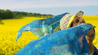 Happy woman holding scarf on rapeseed's field, steadycam shot, slow motion shot