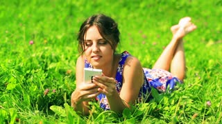 Happy woman in blue dress lying on the meadow and talking on cellphone