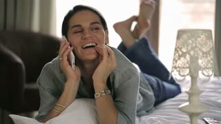Happy woman lying on the bed and talking on cellphone