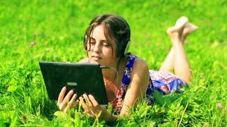 Happy woman lying on the meadow headphones and watching something on tablet
