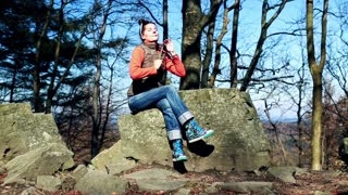 happy woman relaxing and sitting on a stone in the forest