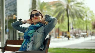Happy woman sitting on the bench in the city and relaxing, steadycam shot