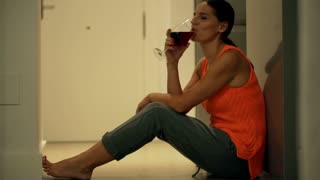Happy woman sitting on the floor and drinking red wine